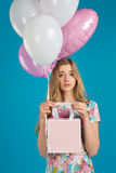 Το γλυκό συμπαθητικό κορίτσι με τα baloons και τα μικρά prersents τοποθετούν σε σάκκο στα χέρια στο μπλε υπόβαθρο 9 πολύχρωμες ει Στοκ Φωτογραφίες