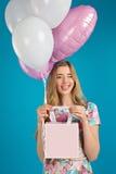 Το γλυκό συμπαθητικό κορίτσι με τα baloons και τα μικρά prersents τοποθετούν σε σάκκο στα χέρια στο μπλε υπόβαθρο Στοκ Φωτογραφίες