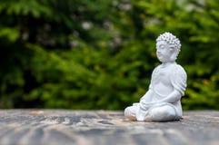 Το γλυπτό του Βούδα γίνεται διαφωτισμένο στο πράσινο υπόβαθρο Έννοια γιόγκας και περισυλλογής Στοκ Φωτογραφία