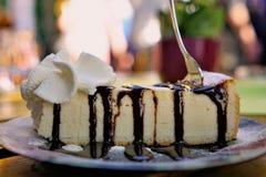 Το δίκρανο που κολλήθηκε γαστρονομικό cheesecake, σάλτσα σοκολάτας, κτύπησε την κρέμα - κινηματογράφηση σε πρώτο πλάνο στοκ εικόνες