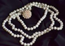 Το δαχτυλίδι και το περιδέραιο των άσπρων μαργαριταριών βρίσκονται στο μαύρο ύφασμα στοκ φωτογραφίες