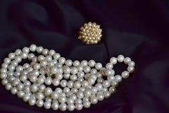 Το δαχτυλίδι και το περιδέραιο των άσπρων μαργαριταριών βρίσκονται στο μαύρο ύφασμα στοκ εικόνες με δικαίωμα ελεύθερης χρήσης