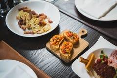 Το δευτερεύον πιάτο είναι καναπεδάκια, το ψημένο στη σχάρα κάλυμμα ψωμιού με τη σάλτσα που γίνεται κοντά χωρίζει σε τετράγωνα το  Στοκ Εικόνες