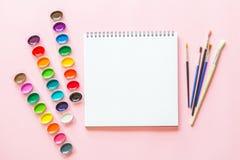 Το δημιουργικό επίπεδο βάζει των παλετών watercolor, βούρτσες χρωμάτων, η Λευκή Βίβλος Εργασιακός χώρος καλλιτεχνών σε ένα ρόδινο στοκ εικόνα με δικαίωμα ελεύθερης χρήσης