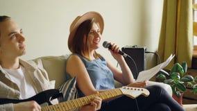 Το δημιουργικό μουσικό ντουέτο ασκεί στο σπίτι τη γυναίκα τραγουδά στο μικρόφωνο και ο άνδρας παίζει την κιθάρα Νέος εύθυμος απόθεμα βίντεο