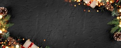 Το δημιουργικό πλαίσιο σχεδιαγράμματος φιαγμένο από έλατο Χριστουγέννων διακλαδίζεται, κώνοι πεύκων, δώρα στο σκοτεινό υπόβαθρο μ στοκ εικόνα με δικαίωμα ελεύθερης χρήσης