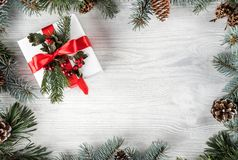 Το δημιουργικό πλαίσιο φιαγμένο από έλατο Χριστουγέννων διακλαδίζεται στο άσπρο ξύλινο υπόβαθρο με το κιβώτιο δώρων, κώνοι πεύκων στοκ φωτογραφίες