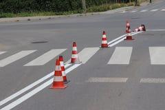Το διαγώνιος-διακοσμημένο για τους πεζούς πέρασμα με το ακόμα μην στεγνωμένο κόκκινο Περιορισμός της κυκλοφορίας από τα οδικά σημ Στοκ φωτογραφία με δικαίωμα ελεύθερης χρήσης