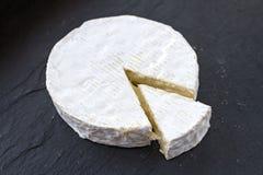 Το διαμορφωμένο καρυκευμένο ελβετικό Camembert τυρί και μια τριγωνική φέτα από το σε ένα μαύρο υπόβαθρο Στοκ Εικόνες