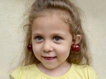 Το διασκεδάζοντας κορίτσι με τα μούρα γλυκών κερασιών ως σκουλαρίκια στα αυτιά Πορτρέτο στοκ φωτογραφία