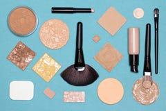 Το διορθωτικό επίπεδο makeup βάζει το σύνολο στην μπλε επιφάνεια Στοκ Φωτογραφία