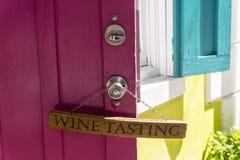 Το δοκιμάζοντας σημάδι κρασιού κρεμά σε μια πορφυρή πόρτα Στοκ Εικόνες