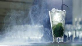 Το δροσίζοντας ποτό με τους κύβους και την πρασινάδα πάγου στο διαφανές γυαλί με τα μαύρα πλαστικά άχυρα στέκεται στο φραγμό στην φιλμ μικρού μήκους