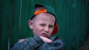 Το δροσερό αγόρι αλλάζει τις εκφράσεις του προσώπου, τοποθέτηση παιδιών στη κάμερα κοντά παλαιό σε ξύλινο φιλμ μικρού μήκους