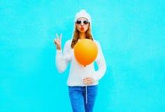Το δροσερό κορίτσι μόδας κρατά το μπαλόνι σε ένα άσπρο καπέλο, πουλόβερ στο μπλε Στοκ Φωτογραφία