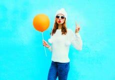 Το δροσερό κορίτσι μόδας κρατά το μπαλόνι σε ένα άσπρο καπέλο στο μπλε Στοκ φωτογραφία με δικαίωμα ελεύθερης χρήσης