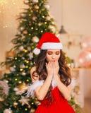 Το δροσερό συμπαθητικό cutie με τη σγουρή σκοτεινή τρίχα στέκεται σε ένα φωτεινό δωμάτιο με ένα διακοσμημένο χριστουγεννιάτικο δέ στοκ εικόνα