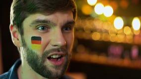 Το δυστυχισμένο αρσενικό με τη γερμανική σημαία χρωμάτισε στο μάγουλο κάνοντας facepalm, χάνοντας παιχνίδι ομάδων απόθεμα βίντεο