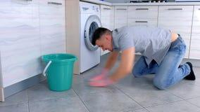 Το δυστυχισμένο κουρασμένο άτομο στα λαστιχένια γάντια πλένει και τριψίματα σκληρά το πάτωμα στην κουζίνα, καθμένος στο πάτωμα, π φιλμ μικρού μήκους