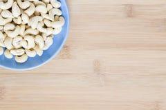 Το δυτικό ανακάρδιο στο μπλε πιάτο στο ξύλινο υπόβαθρο Ακατέργαστο καρύδι των δυτικών ανακαρδίων για τα τρόφιμα Στοκ φωτογραφίες με δικαίωμα ελεύθερης χρήσης