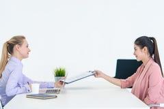 Το δόσιμο γυναικών επαναλαμβάνει στον ανώτερο υπάλληλο για τη συνέντευξη εργασίας στοκ φωτογραφία