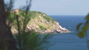 Το δύσκολο νησί κάλυψε τις πράσινες εγκαταστάσεις και το μπλε τοπίο θάλασσας στον ορίζοντα Τοπίο θάλασσας και δύσκολος απότομος β απόθεμα βίντεο