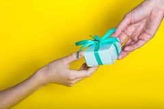το δώρο δίνεται στον παραλήπτη σε ένα κίτρινο υπόβαθρο στοκ εικόνα