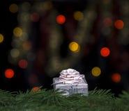 Το δώρο του ρόδινου χρώματος με ένα τόξο στο έλατο διακλαδίζεται σε ένα κλίμα των κίτρινων και κόκκινων φω'των bokeh σε ένα μαύρο Στοκ φωτογραφία με δικαίωμα ελεύθερης χρήσης