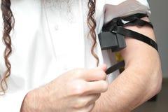 Το εβραϊκό άτομο που τυλίγεται στο tefillin προσεύχεται Ένας θρησκευτικός ορθόδοξος Εβραίος με το βραχίονας-tefillin στο αριστερό Στοκ Φωτογραφίες