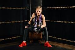 Το εγκιβωτίζοντας κορίτσι μόδας στο σπάσιμο κάθεται σε μια καρέκλα που στηρίζεται σε ένα εγκιβωτίζοντας δαχτυλίδι ανταγωνισμού Στοκ Φωτογραφία