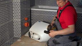 Το ειδικευμένο άτομο υδραυλικών έκοψε το σωλήνα με το μύλο γωνίας για την ένωση του τηγανιού κύπελλων τουαλετών απόθεμα βίντεο