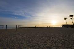 Το ειρηνικό ηλιοβασίλεμα στην πετοσφαίριση άμμου παραλιών πιάνει τους φοίνικες στοκ εικόνες