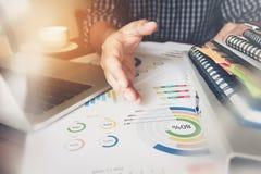 Το λειτουργώντας lap-top χεριών επιχειρηματιών στο ξύλινο γραφείο, χρησιμοποιεί συνοδεύει το άρθρο στη χρηματοδότηση Στοκ εικόνα με δικαίωμα ελεύθερης χρήσης
