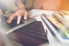 Το λειτουργώντας lap-top χεριών επιχειρηματιών στο ξύλινο γραφείο, χρησιμοποιεί συνοδεύει το άρθρο στη χρηματοδότηση Εκλεκτής ποι Στοκ εικόνα με δικαίωμα ελεύθερης χρήσης
