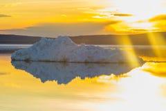 Το λειώνοντας παγόβουνο στη λίμνη βουνών άνοιξη στον ήλιο ρύθμισης Στοκ Εικόνες