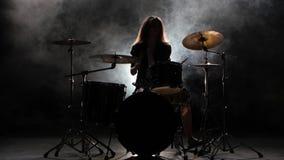 Το ειδικά εκπαιδευμένο κορίτσι παίζει τα τύμπανα Μαύρο υπόβαθρο καπνού σκιαγραφία απόθεμα βίντεο