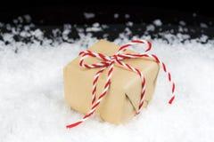 Το εκλεκτής ποιότητας έγγραφο τύλιξε το δώρο που δέθηκε με τον κόκκινο και άσπρο ριγωτό σπάγγο Στοκ Εικόνα