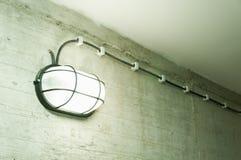 Το εκλεκτής ποιότητας βιομηχανικό φανάρι με το πλέγμα μετάλλων ασφάλειας σύνδεσε στο συμπαγή τοίχο grunge με τη λάμπα φωτός που α Στοκ φωτογραφίες με δικαίωμα ελεύθερης χρήσης