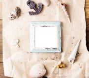 Το εκλεκτής ποιότητας ξύλινο πλαίσιο φωτογραφιών σε χαρτί τεχνών με τα κοχύλια άμμου και θάλασσας χλευάζει επάνω στοκ εικόνες