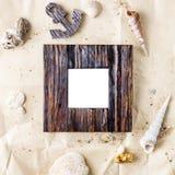 Το εκλεκτής ποιότητας ξύλινο πλαίσιο φωτογραφιών σε χαρτί τεχνών με τα κοχύλια άμμου και θάλασσας χλευάζει επάνω στοκ φωτογραφία