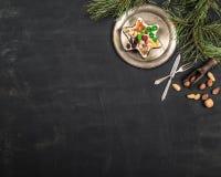 Το εκλεκτής ποιότητας πιάτο, το κουτάλι και το δίκρανο, τα καρύδια, τα γλυκά και το πεύκο διακλαδίζονται στο ξύλινο μαύρο υπόβαθρ στοκ εικόνες με δικαίωμα ελεύθερης χρήσης