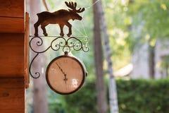 Το εκλεκτής ποιότητας ρολόι οδών ύφους με το σημάδι ελαφιών μετάλλων κρέμασε σε έναν ξύλινο τοίχο κούτσουρων με το πράσινο πάρκο  Στοκ εικόνες με δικαίωμα ελεύθερης χρήσης
