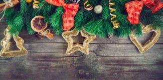 Το εκλεκτής ποιότητας υπόβαθρο Χριστουγέννων με το έλατο διακλαδίζεται, νέο ντεκόρ έτους, παιχνίδια, γλασαρισμένα φρούτα και καρυ Στοκ Φωτογραφίες