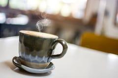 Το εκλεκτής ποιότητας φλυτζάνι χρώματος με το βράσιμο στον ατμό της συνεδρίασης καφέ στον άσπρο πίνακα με το θολωμένο υπόβαθρο κα Στοκ Φωτογραφία