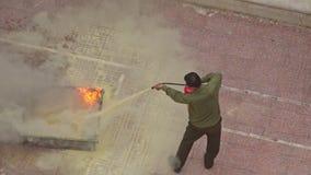 Το εκπαιδευτικό άτομο πυροσβεστικής κινηματογραφήσεων σε πρώτο πλάνο εξαφανίζει την πρότυπη πυρκαγιά