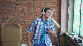 Το εκφραστικό εύθυμο άτομο πορτρέτου στο πουκάμισο και τα ακουστικά τραγουδά και χορεύει κατά τη διάρκεια των επισκευών απόθεμα βίντεο