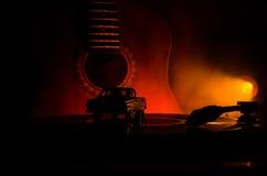 Το εκλεκτής ποιότητας βινυλίου παιχνίδι αρχείων στο φορέα και η ακουστική κιθάρα στο υπόβαθρο με το πορτοκάλι πυρκαγιάς καπνίζουν Στοκ Εικόνες
