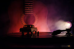 Το εκλεκτής ποιότητας βινυλίου παιχνίδι αρχείων στο φορέα και η ακουστική κιθάρα στο υπόβαθρο με το πορτοκάλι πυρκαγιάς καπνίζουν Στοκ Φωτογραφίες
