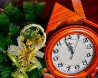Το εκλεκτής ποιότητας ξύλινο ρολόι ενάντια στα Χριστούγεννα ανάβει το υπόβαθρο νέο έτος έννοιας Στοκ Φωτογραφία