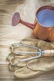 Το εκλεκτής ποιότητας πότισμα μπορεί μέταλλο να μαζεψει με τη τσουγκράνα τα γάντια κηπουρικής στον ξύλινο πίνακα α Στοκ εικόνες με δικαίωμα ελεύθερης χρήσης